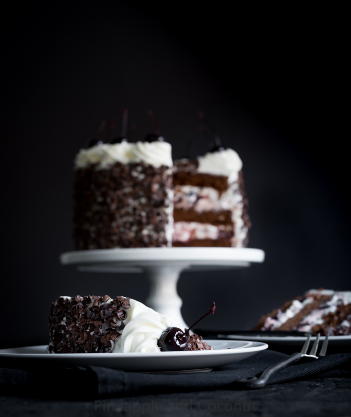 layer cake covered in chocolate curls on a white cake stand, decorated with whipped cream and dark cherries two slices of cake on plates